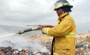 A fireman helps to put out a fire at Riverton City dump