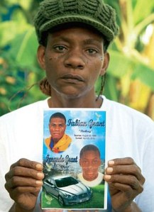Tivoli Gardens resident Majorie Williams holds up photographs of her two sons, who were killed. (Photo: AP/Daily Mail)