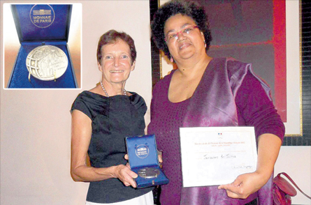Chair of Jamaicans for Justice Susan Goffe receives the medal from the French Ambassador to Jamaica Ginette de Matha.