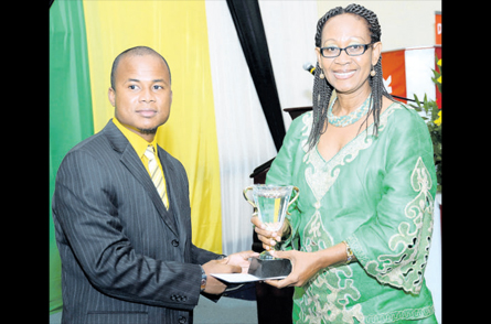 Nationwide News Network reporter George Davis receives the NHT Journalism Award from Hortense Rose, Assistant General Manager for Corporate Communication at the NHT. (Photo: Jamaica Observer)
