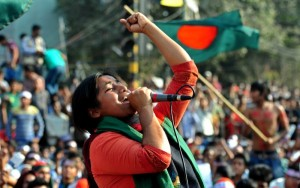 Dhaka, Bangladesh. 11th February 2013 -- Activist Lucky Akter shouts slogans as students from different institutions join the protest demanding the death penalty for all war criminals at Shahbagh in the capital. Many brought flags and banners to continue the four-day protest. -- Shahbagh protesters have called upon their countrymen to observe a three-minute silence from 4:00pm to press home their demands for the death penalty for war criminals.