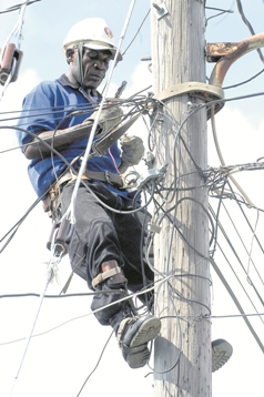 A JPS man disconnects illegal wiring. (Photo: Jamaica Observer)