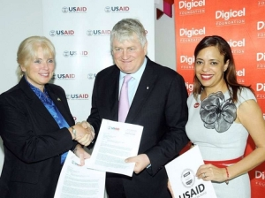 Denis O'Brien, founder and chair of the Digicel Group, seals the deal with Denise Herbol (left), mission director of the United States Agency for International Development, while Samantha Chantrelle, executive director of the Digicel Foundation, looks on. (Photo: Contributed to the Gleaner)
