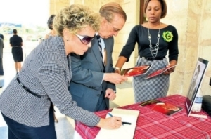 Former Prime Minister Edward Seaga and his wife Carla write in the tribute book for Olive Lewin at her funeral. (Photo: Karl McLarty/Sunday Observer)
