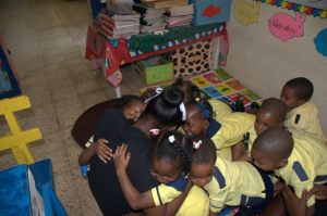Let's hug teacher! The children at Sunrays Educational Centre show some love on Read Across Jamaica Day. (Photo: Crayons Count Facebook page)