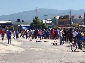 Bodies lie in a parking lot in downtown Kingston on Friday morning. One was reportedly dead and the other remains in hospital, according to newspaper reports. (Photo: Roktowa Facebook page)