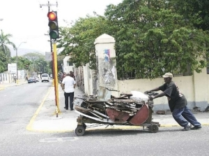 A handcart man with scrap metal pushing his cart in Kingston. The Kingston & St. Andrew Corporation has decided it would like to tax these men, who earn very little. Perhaps they should get themselves unionized.