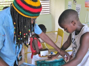 Hands on: a boy at Trench Town Reading Centre learns screen printing. (My photo)