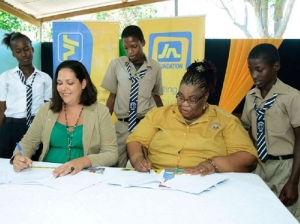 Students of Children First, (from left) Dion Brown, Jomaine Henry, and Akim Porter witness the signing of an agreement between Saffrey Brown (left), general manager, JN Foundation, and Claudette Pious, executive director, Children First, at the Children First offices on Monk Street in Spanish Town, St Catherine, recently. - Contributed
