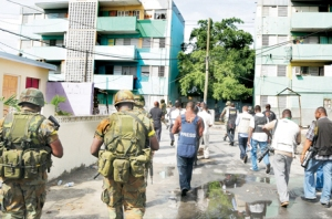 "The Jamaican media on their ""guided tour"" of Tivoli Gardens some days after the so-called incursion by security forces. They were only allowed to walk on certain streets and were escorted by soldiers. I believe that they were they not allowed to interview residents. (Photo: Jamaica Observer)"