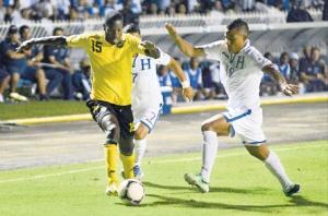 Jamaica's Je-Vaughn Watson eludes two Honduran opponents during last night's World Cup Qualifier in Tegucigalpa. (Photo: Joseph Wellington/Jamaica Observer)