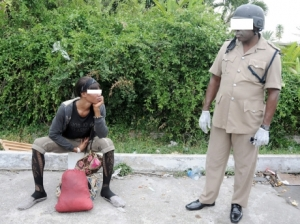 "A policeman with a homeless man who has just been evicted from the house in Millsborough, a very ""posh"" area of Kingston. (Photo: Gleaner)"