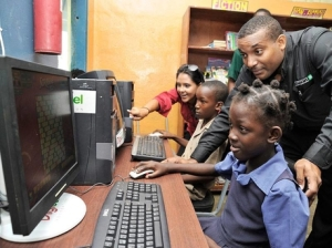 Lindsay Templer (background) of the Digicel Foundation and Karl Gaynor, CEO of the Camara Jamaica Foundation, give Rasheda Samuels (foreground) and Chadane Webb their first lesson on the computer yesterday, after the donation of two computers to the Arcadia Primary School in St Thomas. (Photo: Norman Grindley/Gleaner)