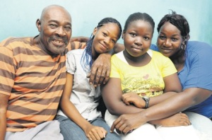 Proud father Gasman Clayton poses with Latonya, his other daughter Caitlon, and Latonya's mother Janice Lewis at their home in Olympic Gardens yesterday. (Phot: Naphtali Junior/Sunday Observer)