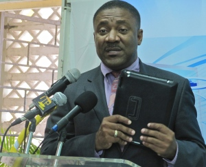 Technology Minister Phillip Paulwell holds up one of the tablets while speaking at a school computer donation. (My photo)