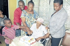 Jane Young is assisted in the cutting of her birthday cake by (left to right) four-year-old Khalil Braham, Patrick Thompson, great-grandson, adopted daughter Veronica Thompson, and Brenda Brown-Cameron who heads the St Andrew Sunrise Cottage on Manning's Hill Avenue. (Photo: Sunday Observer)