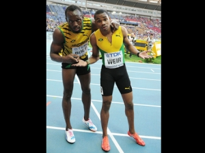 Bringing a smile to your face: Usain Bolt and Warren Weir after finishing with gold and silver medals at the men's 200 meters World Championships in Moscow yesterday. (Photo: Gleaner)