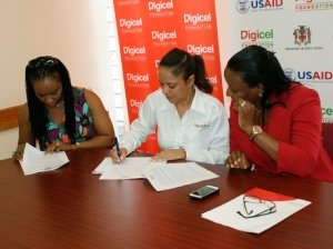 Susan Rattray-Hammond (left), principal of Petersfield Primary in Westmoreland, signs the grant agreement for the expanded phase of the Enrichment Initiative with Samantha Chantrelle (centre), executive director of the Digicel Foundation, and board member Joy Clark.