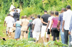 Police and residents walk to the isolated farm where brothers Herman and Norman Rowe were murdered. (Photo: Jamaica Observer)