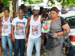 Relatives and friends of brothers Andrew and Triston Brydson and their cousin Kingsley Green wear T-shirts and carry placards bearing pictures of the trio while standing outside the Savanna-la-Mar Resident Magistrate's Court in Westmoreland Thursday. - Photo: Christopher Thomas/Gleaner)