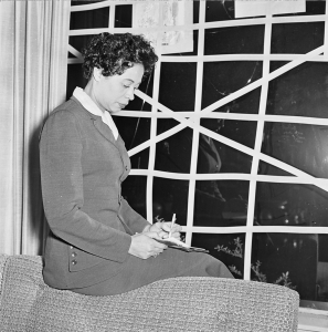 Daisy Bates at her taped-up living room window in Little Rock. Rocks were often thrown through it. (Credit: Gertrude Samuels Collection)