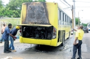 Jamaica Urban Transit Company workers peer inside the burnt-out engine of one of its buses, which caught fire while travelling along Arthur Wint Drive in St Andrew, yesterday. (Photo: Jamaica Observer)
