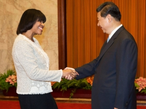 Jamaican Prime Minister Portia Simpson Miller greets Chinese President Xi Jinping for their meeting in Beijing in August. Simpson Miller has talked up the benefits of mega investments by the Chinese, but columnist Claude Clarke says such solutions have never worked where economies are not already competitive. (Photo: AP)