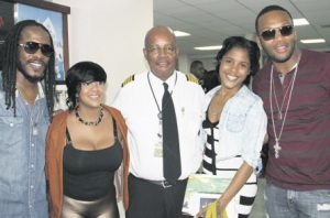 Artistes Wayne Marshall (left), Tifa (second left), Denyque (second right) and Assassin (right) flank Fly Jamaica CEO Capt Ronald Reece at the Cheddi Jagan International Airport in Georgetown Guyana, after the airline's inaugural flight from Kingston to the South American country, on Thursday. (Photo: Noel Grant/Jamaica Observer)