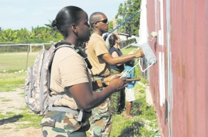 Members of the Jamaica Defence Force work alongside sailors from the Royal Canadian Navy to help paint the computer centre and Internet café. (Photo: Kate Chappell)