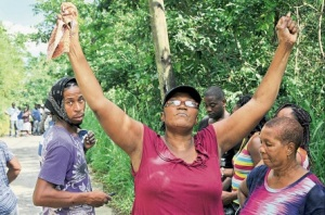 Paulette Dinnal lifts her hands to the heavens as she mourns the murder of her only son, Douglas Folkes, on the Padmore main road in West Rural St Andrew. (Photo: Karl McLarty, Jamaica Observer)