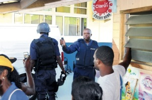 """A policeman threatens to use tear gas to disperse protesters and journalists at the Princess Margaret Hospital in St. Thomas, where the body of reputed """"don"""" Solomon Johnson was taken. Johnson was killed in an alleged shootout with the police. (Photo: Jamaica Observer)"""