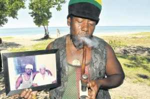 Ras Puddler puffs on a chillum pipe while displaying a photo of himself with the mother of late reggae superstar Peter Tosh, at the 69th birthday celebration of the singer, at Natty's Entertainment Centre at Farm, near Belmont in Westmoreland on Sunday. (Photo: Karl McLarty/Jamaica Observer)