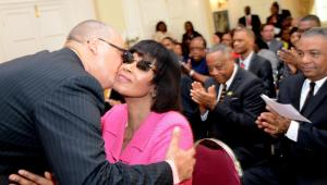 Welcome back: Prime Minister Portia Simpson Miller embraces the newly-reinstated Junior Minister of Transport and Works Richard Azan following the ceremony at King's House on Thursday morning. (Photo: Ricardo Makyn/Gleaner)
