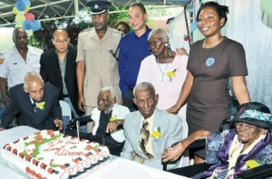 Parade Gardens Centenarians (seated from left) Leon Sylvester Williams, Ruby Hall, Artur Walker, Alberto McDonald, and Virginia Hall (standing, second right) with hosts of a special treat put on for them last Friday (standing from left) Sergeant Carl Simpson of the Gold Street Police Station; Wayne Andrew Tai of A1 Plumbing and Maintenance Services Ltd; Superintendent Victor Hamilton, who heads the Kingston Central police; Don Wehby, group CEO of GraceKennedy Limited; and Susan Moore (right), director of recipient services at Food for the Poor. The treat, which was themed the 'Centenarians of Parade Gardens', was held at the learning Institute of Central Kingston on Tower Street in downtown Kingston. (Photo: Karl McLarty/Jamaica Observer)