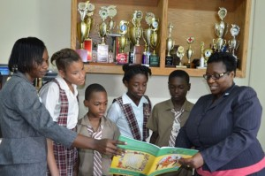 Principal of the St. James-based John Rollins Success Primary School, Yvonne Miller-Wisdom (right), along with teacher and Coordinator of the Reading Marathon, Verena Wellington (left), point out features in a reading book to students (from 2nd left): Anya Bernard, Patroy Vernon, Toniann Cowan, and Sebert Walker. (Photo: Jamaica Information Service)