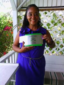 Tamika Pommells Williams poses with the Certificate of Excellence from TripAdvisor. (Photo: Facebook)