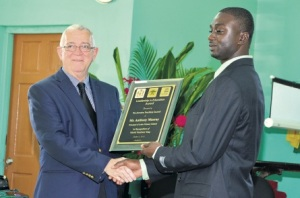 Principal of the Lethe Primary and Infant School in St James, Anthony Murray (right), accepts the Jamaica Teaching Council/Ministry of Education and the United Nations Educational, Scientific and Cultural Organisation (UNESCO) Leadership in Education Award, from Minister of Education, Ronald Thwaites, at a recent ceremony at the school. (Photo: Jamaica Observer)