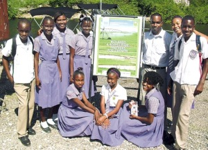 Members of Bustamante High School's Environmental Club and their advisor and coach Dilip Ragoo (third right) gather for a group shot on the banks of Salt River with the Braselletto Mountains rising in the background, after beating Old Harbour High at a World Wetlands Day debate organized by the Caribbean Coastal Area Management Foundation (C-CAM), which manages the Portland Bight Protected Area. (Photo: Jamaica Observer)