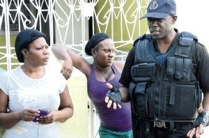 A policeman from the Greater Portmore Police Station offers his condolences to grieving neighbours of John-Michael Hett who was shot dead in the community of Portsmouth on Monday night. (Photo: Joseph Wellington/Jamaica Observer)