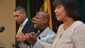 Bishop Delford Davis (center) holds hands with Opposition Leader Andrew Holness and Prime Minister Portia Simpson Miller at the 35th National Prayer Breakfast this week. (Photo: RJR)