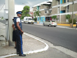 On guard outside Orange Villa: INDECOM's white van is parked near the scene of the shooting. (My photo, taken when I left the Cemetery)