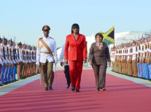 Prime Minister Portia Simpson Miller (centre), inspects the Guard of Honour, formed by the Cuban Military, on her arrival at the Jose Marti International Airport in Havana, Cuba, on Sunday. – Photo by Yhomo Hutchinson (JIS)