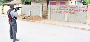 A police officer takes footage of the anti-crime graffiti in Denham Town, which they clearly approve of. Are they going to paint it out? (Photo: Jamaica Observer)