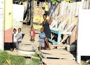 A woman and children mill about a section of Greenwich Town earmarked for better housing under a Food For The Poor and the Constituency Development Fund programme. (Photo: Michael Gordon/Jamaica Observer)