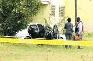 Crime scene investigators look at the motorcar in which Rohan Newman was shot and killed at Molynes Road yesterday. (Photo: Michael Gordon/Jamaica Observer)