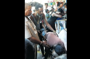Granville Taylor hugs the lifeless body of his father 68-year-old Rudolph Taylor, after he was shot in the chest at his tailor shop on Matthews Lane by gunmen yesterday morning, while police and a neighbour try to pull him away. (Photo: Jamaica Observer)