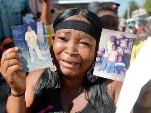 Alicia Dixon, with photos of her 19-year-old brother Tevin Davis, who was allegedly shot and killed by the police in Denham Town, Kingston, on Thursday. (Photo: Norman Grindley/Gleaner)