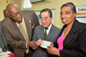 Minister of Health, Hon. Dr. Fenton Ferguson (left), takes a close look at the $11 million cheque, which Ambassador of Japan to Jamaica, His Excellency Yasuo Takase, (centre) is presenting to Executive Director, Jamaica Society for the Blind (JSB), Lola Marson. The money will go towards the building of the low vision resource centre at the JSB's premises in St. Andrew. The signing ceremony for the grant assistance was held on February 20, at the Lion's Club Resource Centre in Mona. (Photo: JIS)
