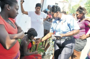 Sympathy: A policewoman offers a drink to Jacqueline Shawna Russell who lost all her possessions in a fire in East Kingston. Russell was one of 13 victims of the blaze. (Photo: Karl McLarty/Jamaica Observer)