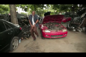 "Shaking a leg in the mechanic's yard - a still from the awesome ""Jamaica Happy"" video with Pharrell's song."
